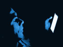 La luce blu e una persona che osserva un monitor al buio